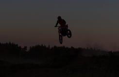 Silueta borrosa del jinete del motocrós que salta en la montaña en puesta del sol Fotografía de archivo libre de regalías