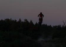 Silueta borrosa del jinete del motocrós que salta en la montaña en puesta del sol Imágenes de archivo libres de regalías