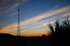 Silueta celular de la torre en la puesta del sol Fotografía de archivo