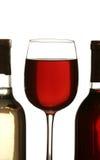 Silueta colorida del vidrio de vino rojo entre la botella de vino dos Fotografía de archivo libre de regalías