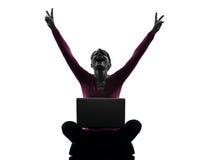 Silueta computacional feliz del ordenador portátil de la mujer que gana Imagen de archivo libre de regalías
