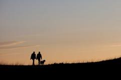 Silueta con los pares que caminan con el perro Fotografía de archivo