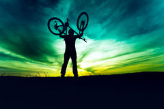 Silueta, contorno de la bici de levantamiento y de la celebración del byciclist Acción de la competencia que gana de la gente ace Fotos de archivo libres de regalías