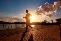 Silueta corriente del hombre en tiempo de la puesta del sol Imágenes de archivo libres de regalías