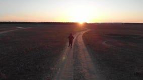 Silueta corriente del hombre en tiempo de la puesta del sol Funcionamiento a campo través al aire libre El hombre joven atlético  almacen de video