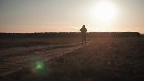 Silueta corriente del hombre en tiempo de la puesta del sol Funcionamiento a campo trav?s al aire libre El hombre joven atl?tico  almacen de video