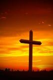 Silueta cruzada cristiana durante puesta del sol Fotos de archivo
