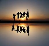 Silueta de amigos en la puesta del sol Imágenes de archivo libres de regalías