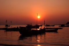Silueta de barcos en la puesta del sol foto de archivo