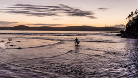 Silueta de Bodyboarder del paisaje marino de la alba foto de archivo