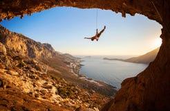Silueta de caer del escalador de roca de un acantilado Fotografía de archivo