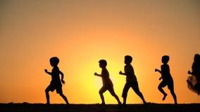 Silueta de cinco niños que corren contra puesta del sol