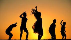 Silueta de cinco niños que saltan contra puesta del sol