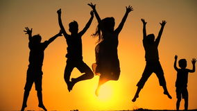 Silueta de cinco niños que saltan junto en la puesta del sol almacen de video