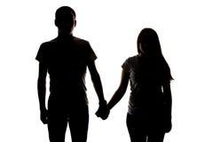 Silueta de dos adolescentes que llevan a cabo las manos Imagen de archivo