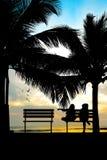 Silueta de dos amigos que se sientan en el banco de madera cerca de la playa Imágenes de archivo libres de regalías