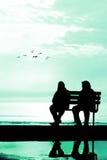Silueta de dos amigos que se sientan en el banco de madera cerca de la playa Imagen de archivo libre de regalías
