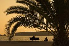 Silueta de dos amigos que se sientan en el embarcadero en la puesta del sol Imagen de archivo libre de regalías