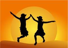 Silueta de dos chicas jóvenes en la puesta del sol Fotografía de archivo libre de regalías