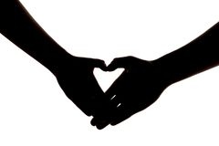 Silueta de dos manos que muestran el corazón Imágenes de archivo libres de regalías