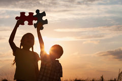 Silueta de dos niños felices que juegan en el campo en t Fotos de archivo