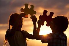 Silueta de dos niños felices que juegan en el campo en t Imágenes de archivo libres de regalías