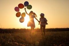 Silueta de dos niños felices que juegan en el campo en t Foto de archivo