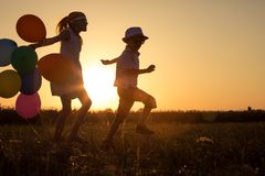Silueta de dos niños felices que juegan en el campo en t Imagen de archivo libre de regalías