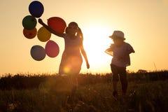 Silueta de dos niños felices que juegan en el campo en t Fotografía de archivo libre de regalías