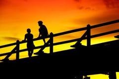 Silueta de dos personas en el puente en la oscuridad Imagen de archivo
