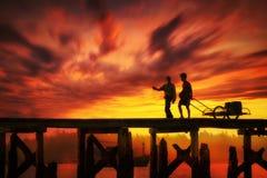 Silueta de dos personas en el puente en la oscuridad Fotos de archivo