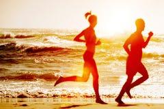 Silueta de dos que corren en la playa Fotos de archivo libres de regalías