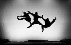 Silueta de gimnastas en el trampolín Imagenes de archivo