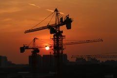 Silueta de grúas contra el cielo de la puesta del sol Foto de archivo libre de regalías