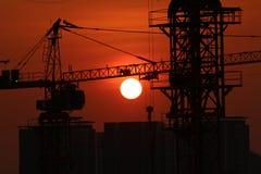 Silueta de grúas contra el cielo de la puesta del sol Fotos de archivo libres de regalías