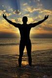 Silueta de hombres atléticos al mar en la puesta del sol Imagen de archivo libre de regalías