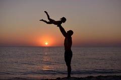 Silueta de jugar el papá y a la hija en el fondo de la puesta del sol del mar fotografía de archivo