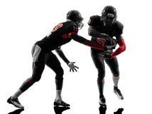 Silueta de la acción del juego de paso de dos jugadores de fútbol americano Imagen de archivo libre de regalías