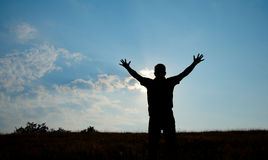 Silueta de la adoración del hombre con las manos aumentadas al cielo en naturaleza Fotografía de archivo