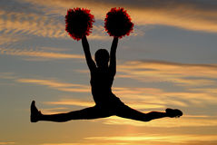 Silueta de la animadora que salta en el aire que hace las fracturas con un su Fotos de archivo libres de regalías