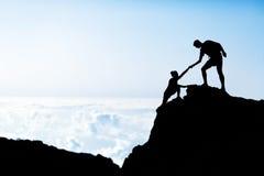 Silueta de la ayuda del hombre y de la mujer en montañas