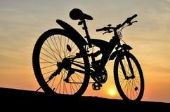 Silueta de la bici de montaña con puesta del sol Fotos de archivo