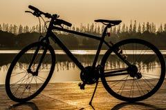 Silueta de la bicicleta cerca del lago y de la puesta del sol en el cielo hermoso Imagen de archivo
