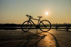 Silueta de la bicicleta cerca del lago y de la puesta del sol en el cielo hermoso Fotografía de archivo