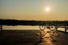 Silueta de la bicicleta cerca del lago y de la puesta del sol en el cielo hermoso Imagen de archivo libre de regalías