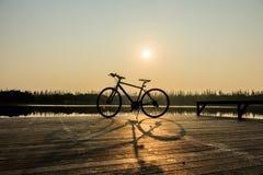 Silueta de la bicicleta cerca del lago y de la puesta del sol en el cielo hermoso Fotos de archivo