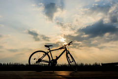Silueta de la bicicleta cerca del lago y de la puesta del sol en el cielo hermoso Imágenes de archivo libres de regalías