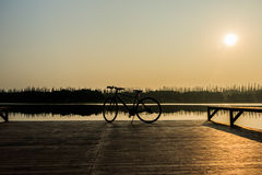 Silueta de la bicicleta cerca del lago y de la puesta del sol en el cielo hermoso Foto de archivo