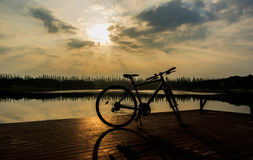 Silueta de la bicicleta cerca del lago y de la puesta del sol en el cielo hermoso Fotografía de archivo libre de regalías