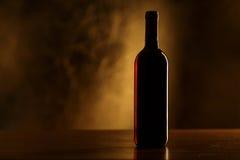 Silueta de la botella de vino rojo en la tabla de madera y el fondo de oro Fotografía de archivo